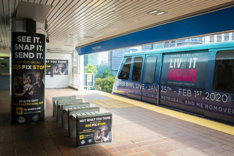 Billboards displaying a campaign against human trafficking are seen at Knight Center Metrorail station as a train depicting the Super Bowl logo arrives at the station in Downtown Miami (AFP Photo/Eva Marie UZCATEGUI)