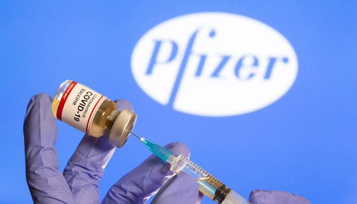 """A woman holds a small bottle labeled with a """"Coronavirus COVID-19 Vaccine"""" sticker and a medical syringe in front of displayed Pfizer logo in this illustration taken, October 30, 2020. REUTERS/Dado Ruvic"""