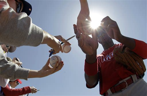 Philadelphia Phillies right fielder Domonic Brown signs autographs for fans before a spring training baseball game in Dunedin, Fla., Monday, March 25, 2013. (AP Photo/Kathy Willens)