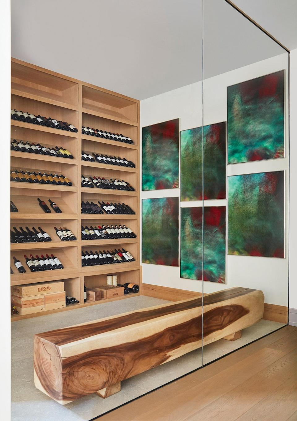 """The wine cellar came with the home, which was designed by Pacific Peninsula Architecture. """"The architect provided us with such great bones to work with,"""" says Legaspi. The artwork on the wall is Double Jicky by Eileen Quinlan, and the wood bench is from Lau's existing collection."""