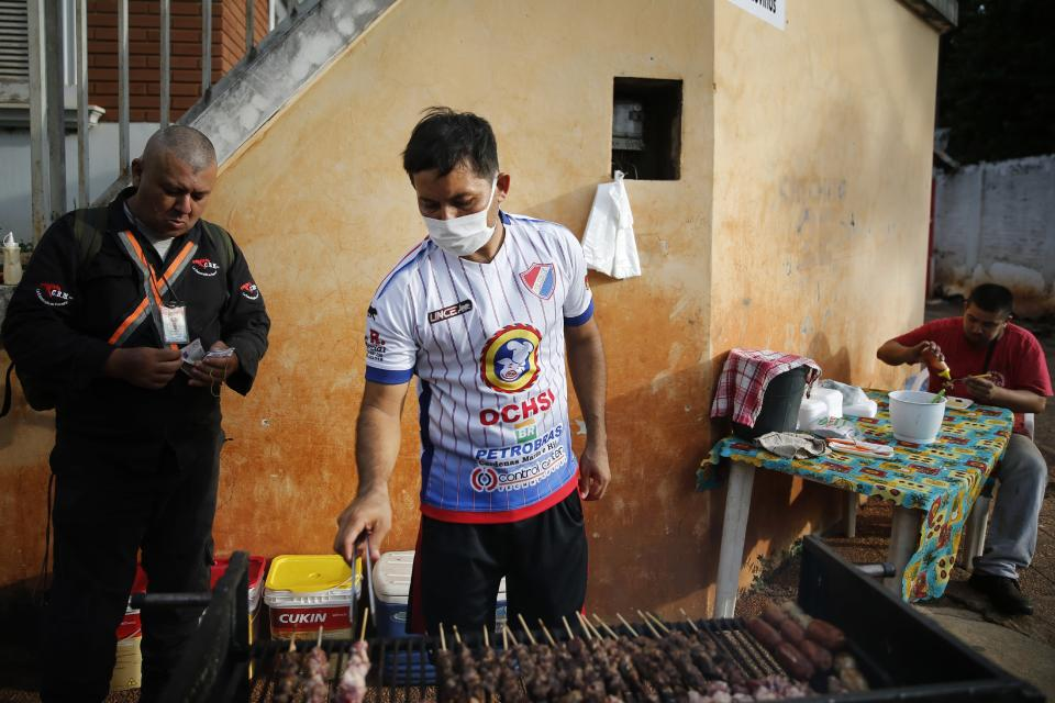 """Striker Nicolas Caballero of the Resistencia football club, second division, roasts """"asadito"""" or beef sticks for sale on a street corner in the San Lorenzo, Paraguay, Tuesday, Feb. 2, 2021. Caballero, 32, who hasn't been paid by his club for more than a year, now has a food stall that sells barbecue on the streets to survive during the COVID-19 pandemic. (AP Photo/Jorge Saenz)"""