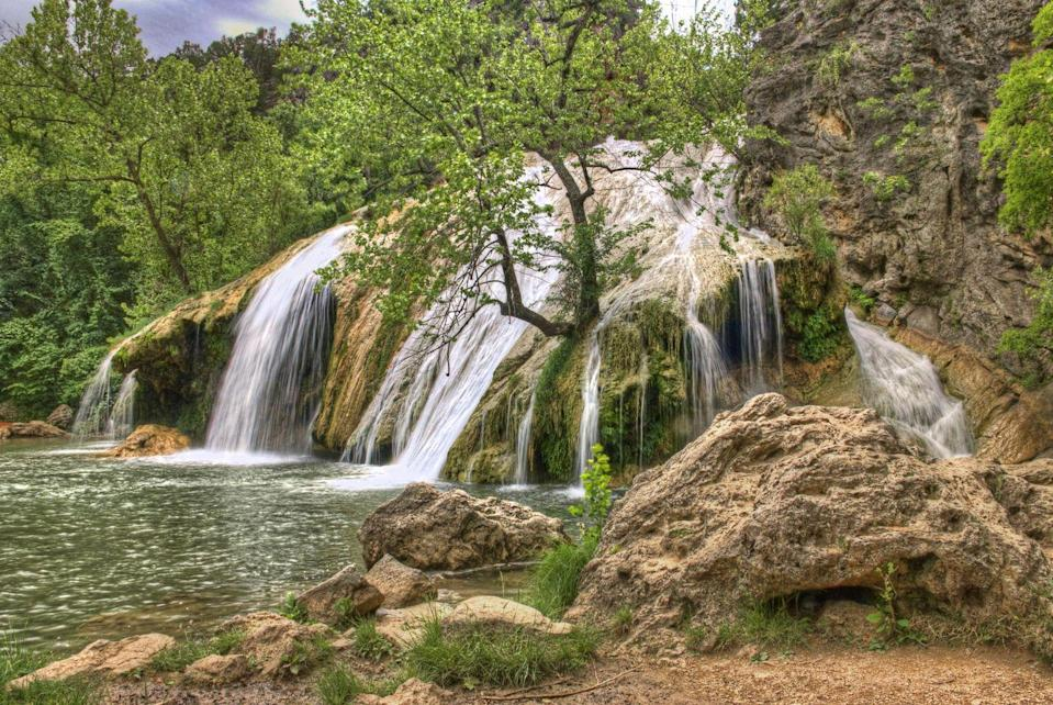"""<p>There's a reason <a href=""""https://www.tripadvisor.com/Attraction_Review-g51303-d117492-Reviews-Turner_Falls_Park-Davis_Oklahoma.html"""" rel=""""nofollow noopener"""" target=""""_blank"""" data-ylk=""""slk:Turner Falls Park"""" class=""""link rapid-noclick-resp"""">Turner Falls Park</a> is a favorite swimming hole for locals: It's home to an impressive 77-foot tall waterfall that you can swim underneath. After taking a dip, explore the rock castle that was built into the hillside nearby.</p>"""