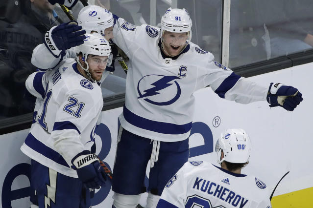 Tampa Bay Lightning center Steven Stamkos (91) celebrates with defenseman Kevin Shattenkirk (22), center Brayden Point (21) and right wing Nikita Kucherov after Shattenkirk scored during the third period of an NHL hockey game against the Boston Bruins, Thursday, Oct. 17, 2019, in Boston. The Lightning won 4-3 in a shootout. (AP Photo/Elise Amendola)