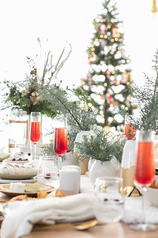 """<p>Who says you have to stick to red and white flowers...or opt for a red and white color scheme at all, for that matter? Here, a collection of different-sized vases filled with evergreen branches look positively sophisticated.</p><p><strong>Get the tutorial at <a href=""""https://sugarandcharm.com/how-to-put-together-a-charming-christmas-brunch"""" rel=""""nofollow noopener"""" target=""""_blank"""" data-ylk=""""slk:Sugar and Charm"""" class=""""link rapid-noclick-resp"""">Sugar and Charm</a>.</strong></p><p><strong><a class=""""link rapid-noclick-resp"""" href=""""https://www.amazon.com/Factory-Direct-Craft-Artificial-Decorating/dp/B076CNVLZB?tag=syn-yahoo-20&ascsubtag=%5Bartid%7C10050.g.644%5Bsrc%7Cyahoo-us"""" rel=""""nofollow noopener"""" target=""""_blank"""" data-ylk=""""slk:SHOP FAUX EVERGREEN"""">SHOP FAUX EVERGREEN</a><br></strong></p>"""