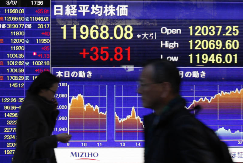 People walk past an electronic board showing the Nikkei 225 index, outside a securities company in Tokyo, Thursday, March 7, 2013. World stock markets were mostly higher Thursday following Wall Street's eye-popping performance this week. Japan's Nikkei 225 index had its highest close in four years. (AP Photo/Shuji Kajiyama)