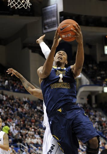 West Virginia's Dominique Rutledge (1) drives to the hoop during the first half of an NCAA college basketball game against Connecticut in Hartford, Conn., on Monday, Jan. 9, 2012. (AP Photo/Fred Beckham)
