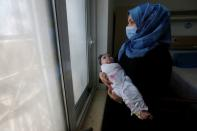 An Iraqi woman wearing a protective mask carries her baby who suffers from cancer at the Children's Hospital for Cancer Diseases in Basra