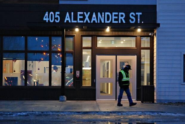 A person walks past the front doors of the Whitehorse Emergency Shelter. Measures have been tightened at the facility following a COVID-19 outbreak. (Philippe Morin/CBC - image credit)