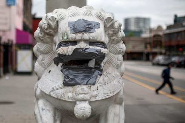 Racist graffiti is covered up by duct tape on the lions at the Millennium Gate in Chinatown in May 2020.