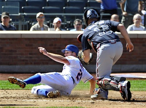 New York Mets' Daniel Murphy, left, slides in safely to home plate under the tag of Atlanta Braves catcher Brian McCann (16) on single by Ike Davis in the fourth inning of a baseball game on Sunday, Sept. 9, 2012, at Citi Field in New York. (AP Photo/Kathy Kmonicek)