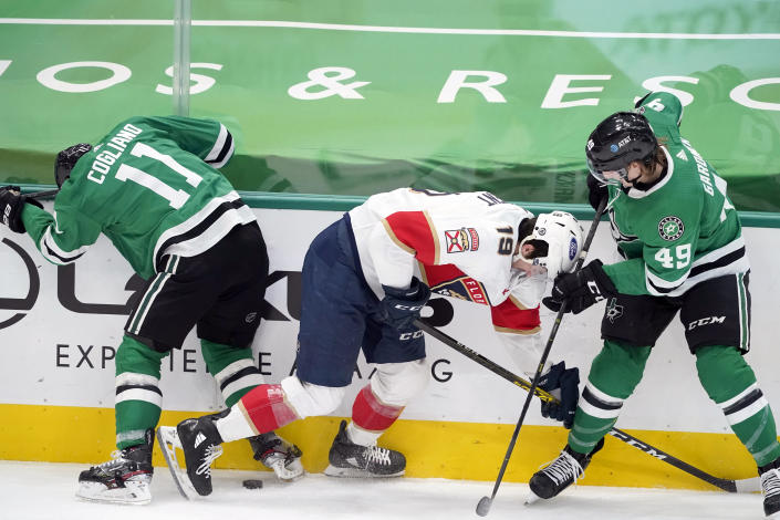 Dallas Stars center Andrew Cogliano (11) and center Rhett Gardner (49) work to control the puck in front of Florida Panthers left wing Mason Marchment (19) in the second period of an NHL hockey game in Dallas, Saturday, April 10, 2021. (AP Photo/Tony Gutierrez)