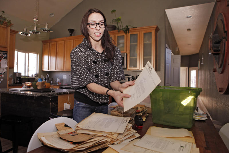 In this photo taken Tuesday, Nov. 20, 2012 Alissa Williams holds a letter addressed to T.K. Pharmacy at her home in Denver. The letter from the early 1940s was found with other documents and letters during renovations at a former Denver pharmacy owned by Japanese-Americans. Some letters arriving from Japanese-American internment camps during World War II were very specific, asking for a certain brand of bath powder, cold cream or cough drops _ but only the red ones. Others were just desperate for anything from the outside world.  (AP Photo/Ed Andrieski)