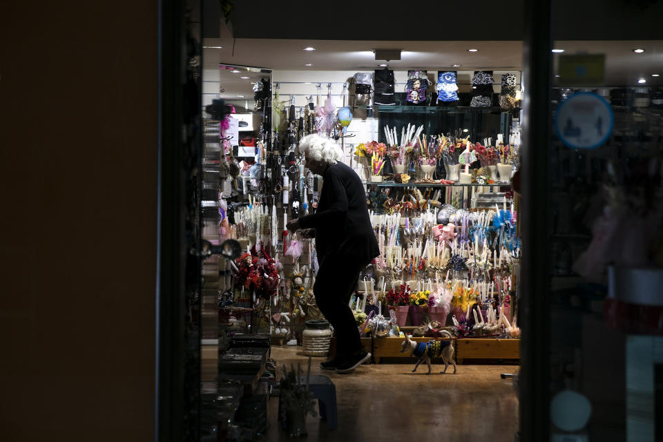 A woman adjusts items inside a shop, at Glyfada suburb west of Athens, Saturday, April 3, 2021. Greece has relaxed some coronavirus restrictions despite surging COVID-19 cases that are straining hospitals to their limits, with retail stores to reopen and people allowed to drive outside their home municipalities for exercise on weekends. AP Photo/Yorgos Karahalis)