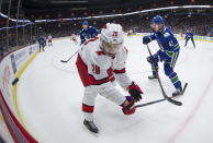 Vancouver Canucks' Quinn Hughes, right, shoots the puck off the boards past Carolina Hurricanes' Sebastian Aho, of Finland, during the first period of an NHL hockey game in Vancouver, British Columbia, Thursday, Dec. 12, 2019. (Darryl Dyck/The Canadian Press via AP)