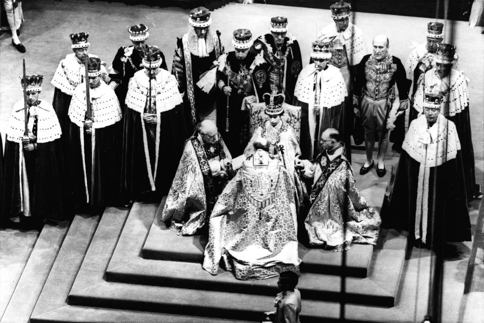 FILE - This June 2, 1953 file photo shows Britain's Queen Elizabeth II, seated on the throne, receiving the fealty of the Archbishop of Canterbury, centre with back to camera, the Bishop of Durham, left and the Bishop of Bath and Wells, during her Coronation in Westminster Abbey. Britain's royal family and television have a complicated relationship. The medium has helped define the modern monarchy: The 1953 coronation of Queen Elizabeth II was Britain's first mass TV spectacle. Since then, rare interviews have given a glimpse behind palace curtains at the all-too-human family within. (AP Photo/File)