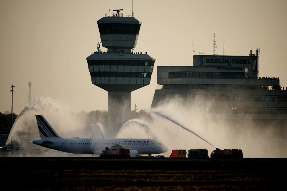 The airport fire brigade at Tegel Airport (TXL) sprayed water fountains on the Airbus of the French airline Air France as a farewell before its take-off for Paris in Berlin, Germany, Sunday, Nov. 8, 2020. Tegel Airport closes with the departure of the last scheduled flight number AF 1235 at 15:00. (Michael Kappeler/dpa via AP)