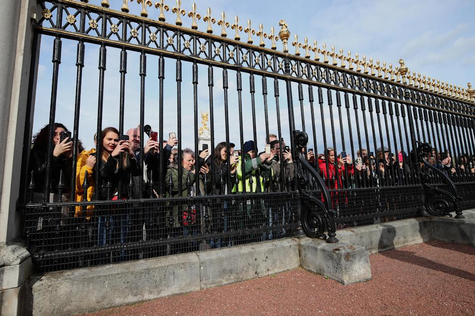 People gather outside Buckingham Palace to take pictures on their mobile phones of the notice placed on an easel in the palace's forecourt in London to formally announce the birth of a baby boy to the Duke and Duchess of Sussex [Photo: PA]