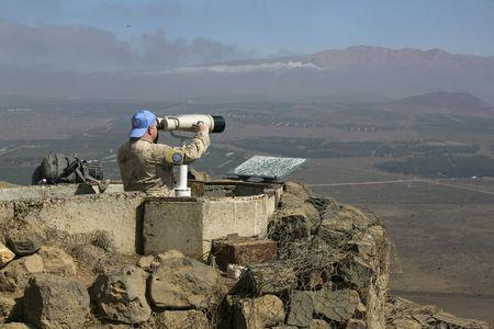 A Canadian member of the United Nations Disengagement Observer Force (UNDOF) looks through binoculars at Mount Bental, an observation post in the Israeli occupied Golan Heights near the ceasefire line between Israel and Syria August 21, 2015. REUTERS/Baz Ratner