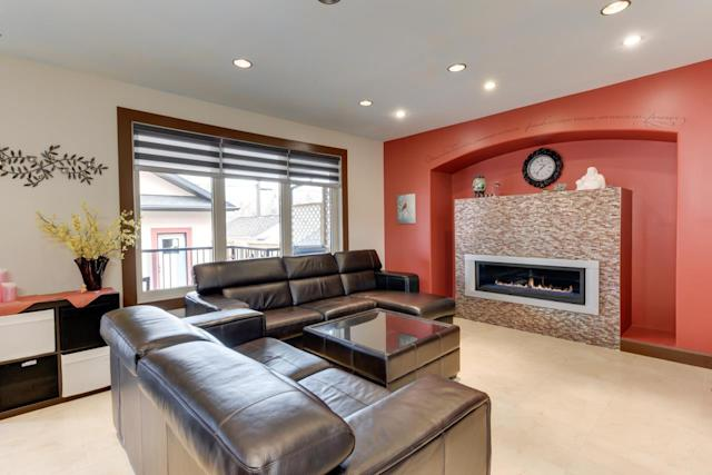 <p><span>11150 72 Avenue Northwest, Edmonton, Alta.</span><br> The living room has a feature wall with a large gas fireplace.<br> (Photo: Zoocasa) </p>