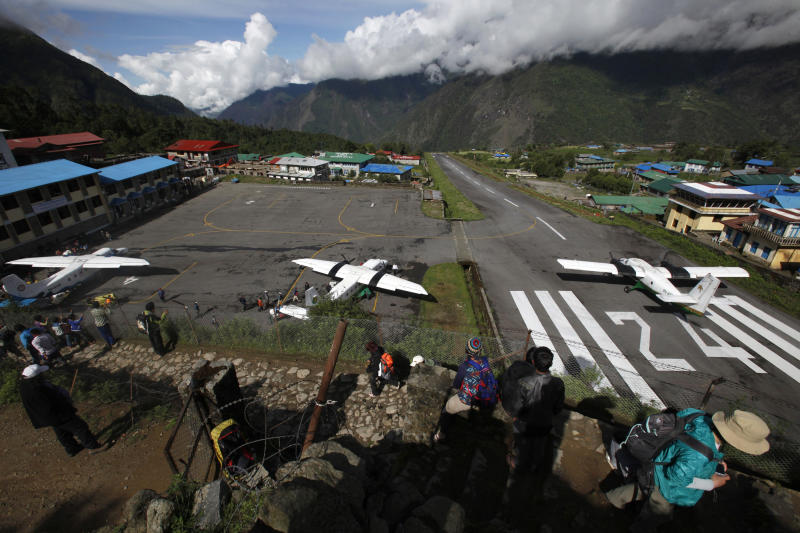 In this Sunday, May 26, 2013 photo, several flights get ready to take off after a couple of days of bad weather disrupted flight services at Lukla airport, Nepal. Carved out of side of a mountain, the airport was built by Sir Edmund Hillary in 1965, and at an altitude of 2,843 meters (9,325 feet) it has earned the reputation of being one of the most extreme and dangerous airports in the world. (AP Photo/Niranjan Shrestha)
