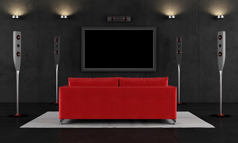 A red couch facing a TV screen in a home theater