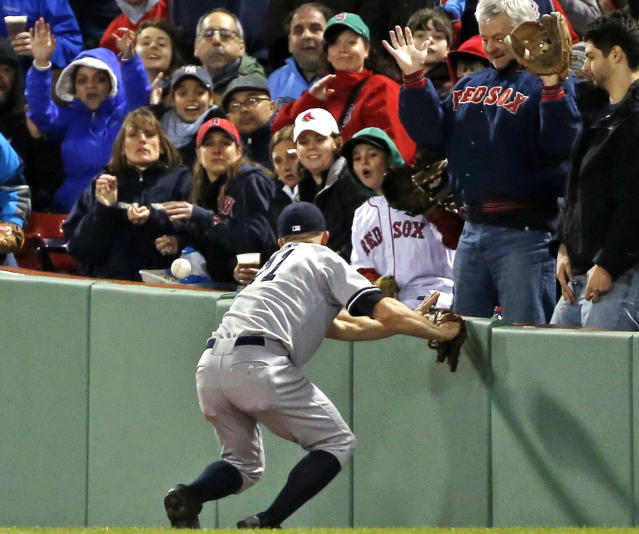 Fans watch as New York Yankees right fielder Brett Gardner cannot make the catch on a ground-rule double by Boston Red Sox's Mike Napoli during the third inning of a baseball game at Fenway Park in Boston, Wednesday, April 23, 2014. Dustin Pedroia scored on the hit. (AP Photo/Elise Amendola)