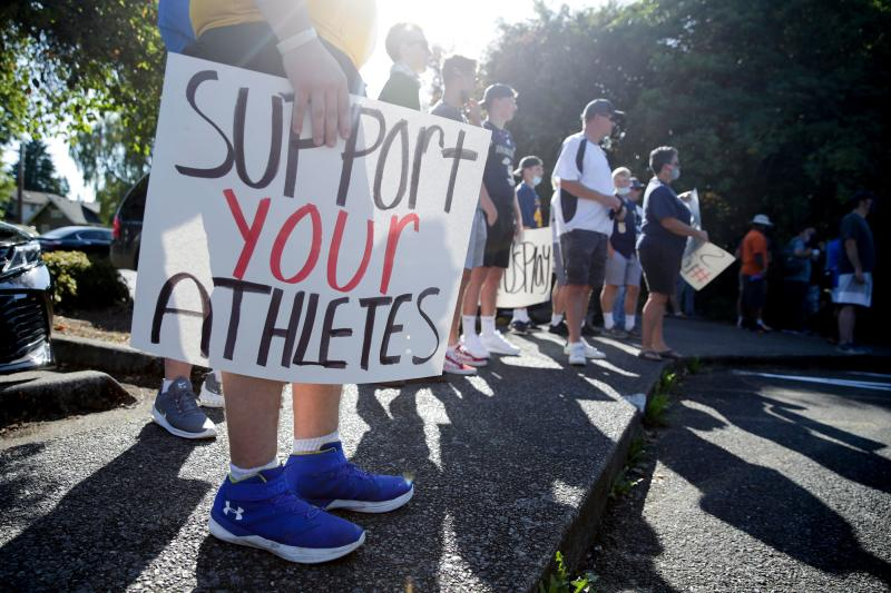 """Athlete Zackery Schmeichel of Hazen High School holds a sign that reads """"support your athletes"""" as people gather for a march and rally organized by Student Athletes of Washington (SAW), a group that formed to protest the postponement of fall sports due to COVID-19, at the state capitol in Olympia, Washington on September 3, 2020. (Photo by JASON REDMOND/AFP via Getty Images)"""