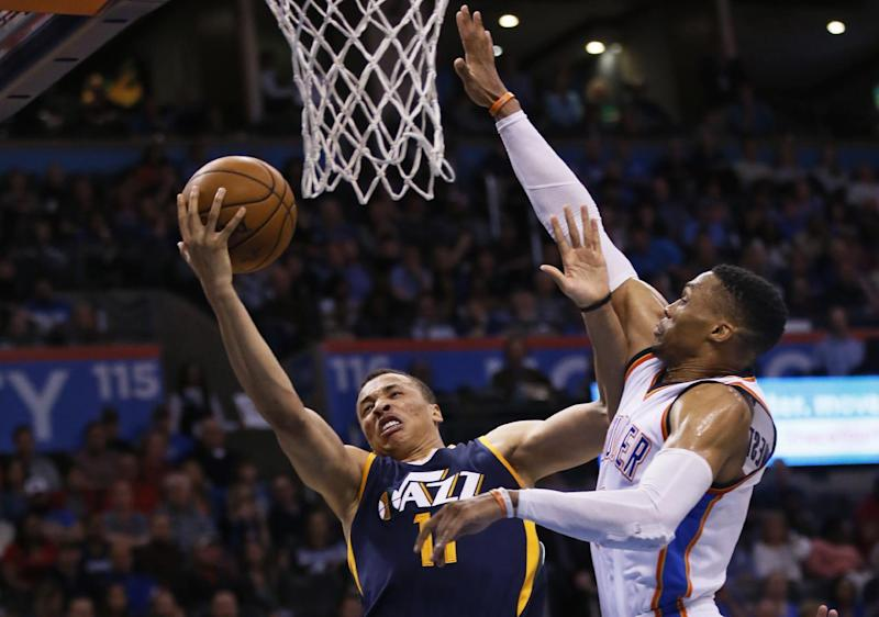 Utah Jazz guard Dante Exum (11) shoots in front of Oklahoma City Thunder guard Russell Westbrook, right, in the fourth quarter of an NBA basketball game in Oklahoma City, Saturday, March 11, 2017. Oklahoma City won 112-104. (AP Photo/Sue Ogrocki)