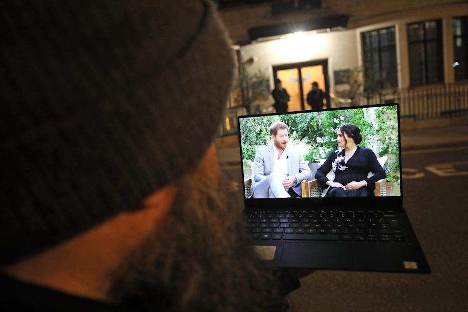 A man watches the Duke and Duchess of Sussex interview with Oprah Winfrey, which is being shown on ITV, on a laptop outside King Edward VII's Hospital, London where the Duke of Edinburgh has been moved to for continuing treatment after his heart surgery at St Bartholomew's Hospital. Picture date: Monday March 8, 2021. (Photo by Yui Mok/PA Images via Getty Images)
