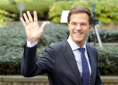 The Netherlands' Prime Minister Mark Rutte waves to the media upon arriving at a European Union leaders summit at the EU council headquarters in Brussels