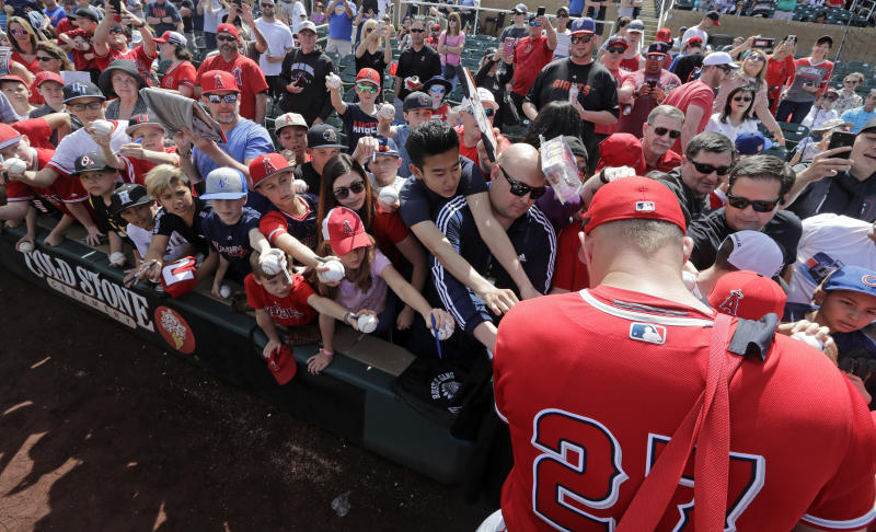 Fans reach toward Los Angeles Angels' Mike Trout in hopes of getting an autograph before a spring training baseball game against the Arizona Diamondbacks, Thursday, March 21, 2019, in Scottsdale, Ariz. (AP Photo/Elaine Thompson)