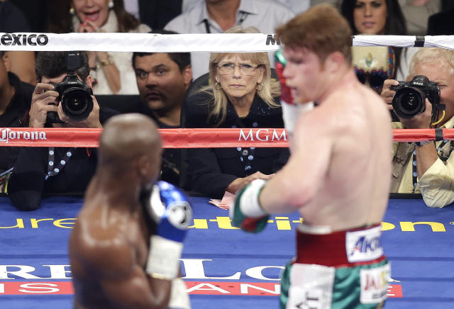 In this photo taken Saturday, Sept. 14, 2012, boxing judge Cynthia C.J. Ross, center, watches as Canelo Alvarez, right, and Floyd Mayweather Jr. move around the ring during a world junior middleweight title fight in Las Vegas. Ross is temporarily stepping away from the ring after drawing widespread criticism for scoring the fight a draw when two other judges scored Mayweather the clear winner. (AP Photo/Isaac Brekken)