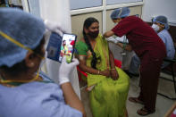 A health worker takes pictures as another administers the Covishield vaccine against the coronavirus at a vaccination program for members of the transgender community in Mumbai, India, Sunday, June 20, 2021. (AP Photo/Rafiq Maqbool)