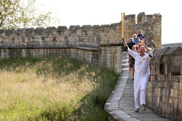YORK, UNITED KINGDOM - JUNE 19: In this handout image provided by LOCOG, Torchbearer 104 Philip Jones carries the Olympic Flame on the York City Walls on the Torch Relay leg through York on June 19, 2012 in York, England. The Olympic Flame is now on day 32 of a 70-day relay involving 8,000 torchbearers covering 8,000 miles. (Photo by LOCOG via Getty Images)
