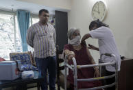 A health worker administers COVID-19 vaccine to an elderly woman who has difficulty in moving around inside their house during a door to door vaccination program in Mumbai, India, Thursday, Aug. 5, 2021. (AP Photo/Rajanish Kakade)