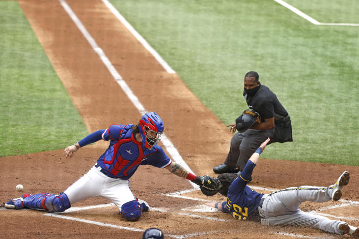 Milwaukee Brewers left fielder Christian Yelich (22) scores in front of Texas Rangers catcher Jonah Heim as home plate umpire Ramon De Jesus watches, during the first inning of a preseason baseball game Tuesday, March 30, 2021, in Arlington, Texas. (AP Photo/Michael Ainsworth)