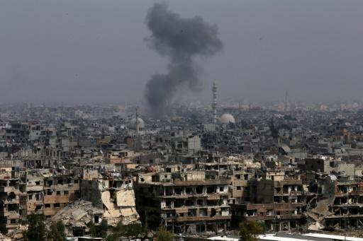 Smoke rises from buildings in Yarmuk, a Palestinian refugee camp on the edge of Damascus, during regime shelling targeting Islamic State group positions in the southern district of the capital on April 28, 2018