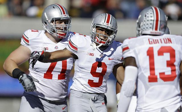 Ohio State's Devin Smith (9) celebrates with quarterback Kenny Guiton (13) and Corey Linsley (71) after Smith scored a touchdown against California during the first quarter of an NCAA college football game, Saturday, Sept. 14, 2013, in Berkeley, Calif. (AP Photo/Ben Margot)