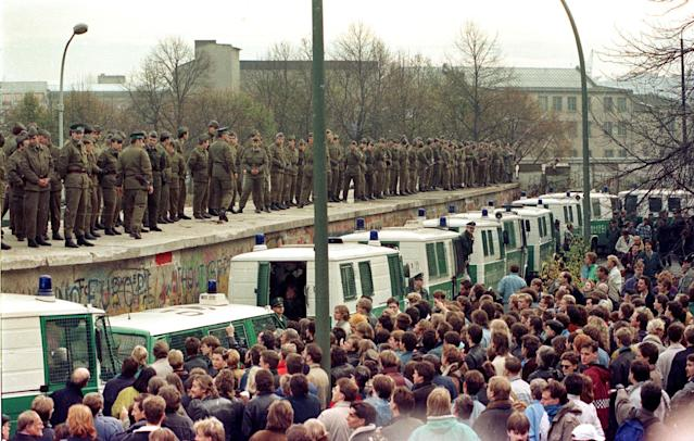 Hundreds of East Berlin border guards stand atop the Berlin Wall at the Brandeburg Gate faced by thousands of West Berliners on Nov. 11, 1989. (Photo: Reuters)