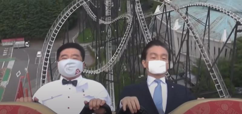 Executives demonstrating the 'no screaming' policy on a rollercoaster in a Japanese theme park (Fuji-Q Highland).