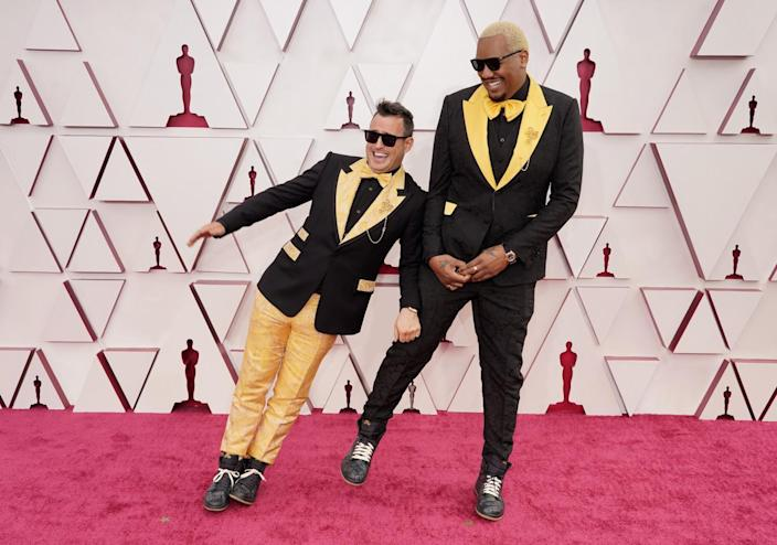 Martin Desmond Roe, left, and Travon Free in yellow and black suits on the red carpet.