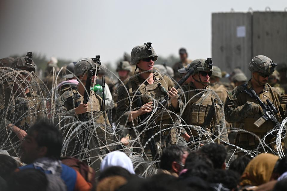 US soldiers stand guard behind barbed wire as Afghans sit on a roadside near the military part of the airport in Kabul on August 20, 2021, hoping to flee from the country after the Taliban's military takeover of Afghanistan. (Wakil Kohsar/AFP via Getty Images)
