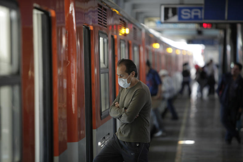 A commuter wears a protective mask to prevent infection from swine flu at a subway station in Mexico City, Friday, May 1, 2009. (AP Photo/Eduardo Verdugo)