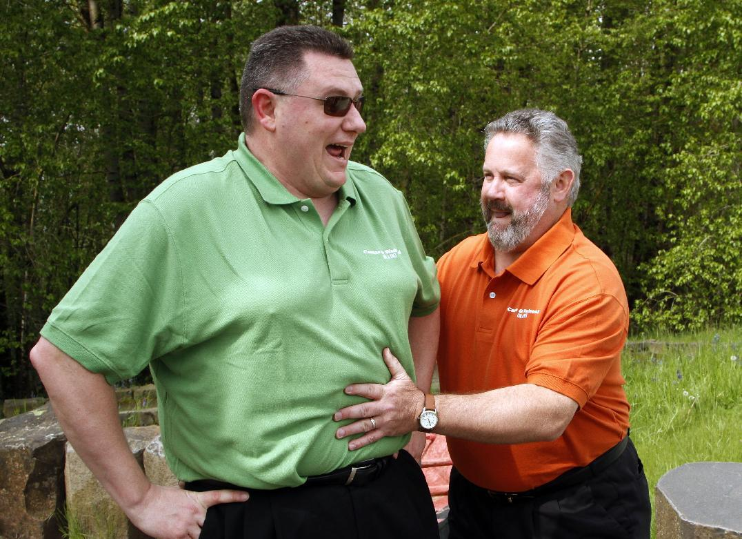"Washougal Mayor Sean Guard, right, feels the stomach of Camas Mayor Scott Higgins before their weigh-in in Washougal, Wash., Wednesday, May 2, 2012. The mayors of the two neighboring Washington state towns on the banks of the Columbia River are embarking on a ""Biggest Loser""style contest to see which of the two communities can lose the most weight in 12 months. (AP Photo/Don Ryan)"
