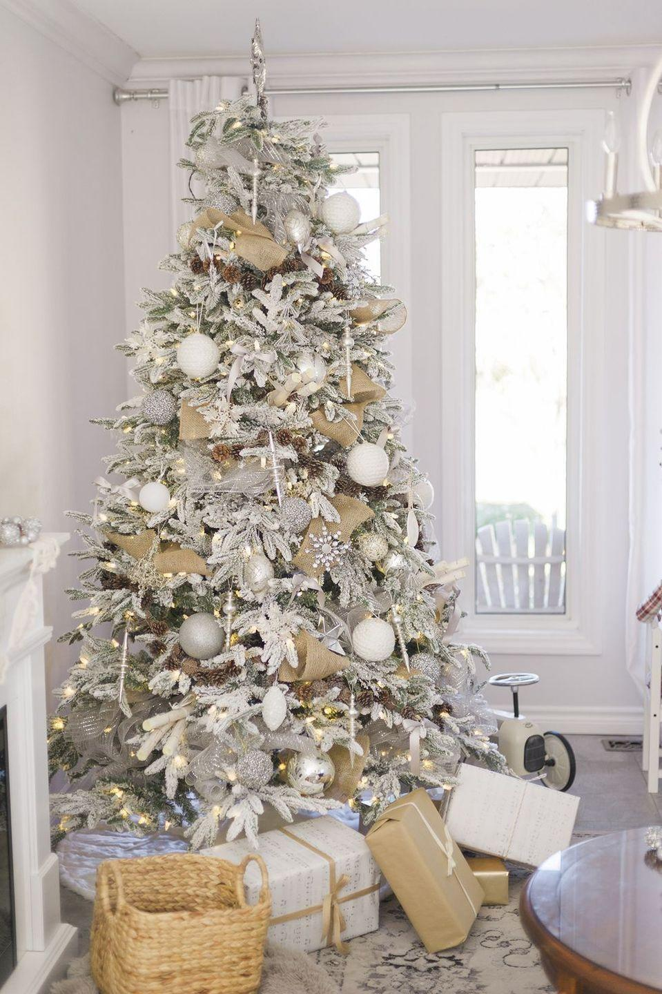 <p>A white palette makes a statement with this Cape Cod–inspired Christmas tree. A snow-dusted look is fully embraced with white ornaments and presents, plus natural woven ribbon and other earthy touches. </p>