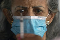 A woman eyes the syringe that will deliver her shot of the Sinovac COVID-19 vaccine at a drive-thru site set up in the Pacaembu soccer stadium parking lot during a priority vaccination program for seniors in Sao Paulo, Brazil, Wednesday, March 3, 2021. (AP Photo/Andre Penner)