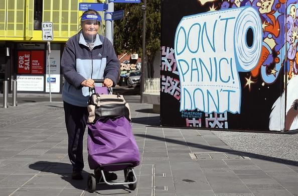 A face shield-clad woman passes a mural while shopping in the Melbourne suburb of Prahran.