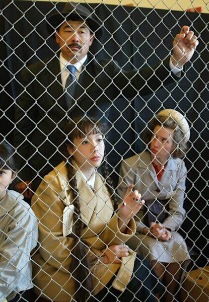Rudy Mano (L), 13-year-old Jaclyn D'Arcy (C) and Holly Ota are detained behind a fence during a re-enactment of the internment of Japanese-Americans (AFP Photo/Mike Fiala)