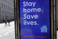 FILE - In this April 2, 2020, file photo, a sign advising people to stay home due to COVID-19 concerns is displayed at a MUNI bus stop in San Francisco. The city has suffered a large exodus, both in housing and people working in offices. When the lockdown order came in March 2020, an estimated 137,500 workers for companies that include Google, Facebook and Uber, seemingly vanished overnight. Moving vans carted off entire households for roomier suburban homes and younger people simply packed up their cars and left since they could work from anywhere. Residential rents plummeted, but are now climbing back up. Rent prices have gone down 10% in San Francisco but remained stable in Los Angeles. (AP Photo/Jeff Chiu, File)