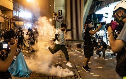 A protester attempts to kick a tear gas canister during a demonstration on Hungry Ghost Festival day in Sham Shui Po district - Credit: Getty